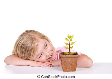 child with plant smiling - Young girl or child with a potted...