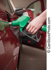 Woman refilling car - Woman hand refilling up gas tank of...