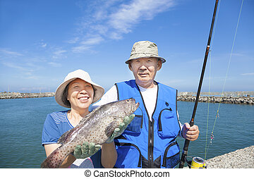happy senior couple go fishing and showing big fish