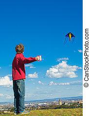 under control  - boy flying a kite