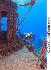 Exploration - Female diver exploring the superstructure of...