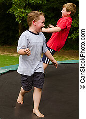 Children playing on trampoline - Children playing while...