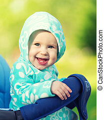 happy little baby girl smiling in a blue hood in the...
