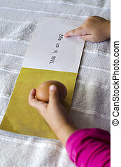 Learning to read English - A hands of a preschooler holds a...