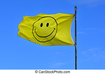 Yellow flag with smiley face wave in the wind on blue sky