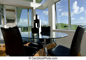 Dining table in a sunroom with large windows and green...
