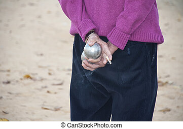 Players bocce ball back with the ball in hand