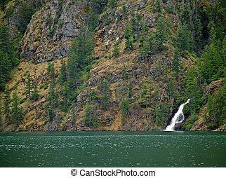 Beautiful Mountain Waterfall Flowing into a Green Lake
