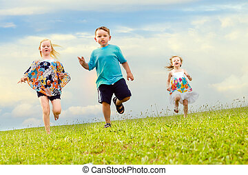 Children having a foot race while running downhill at park