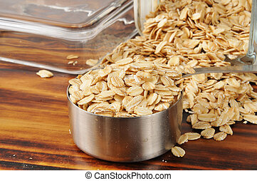 Uncooked rolled oats - A measuring cup of raw rolled oats -...