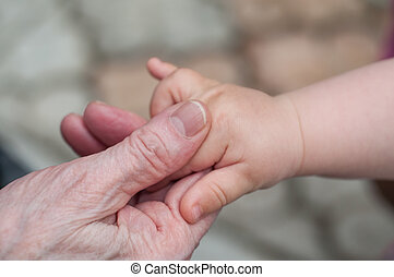 hands of baby grandson and old grandmother, concept of...