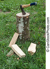 Axe and wooden trees logs after being cut on grass
