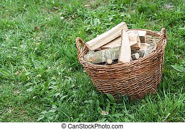 Basket of cut logs fire wood on green grass, environmental...