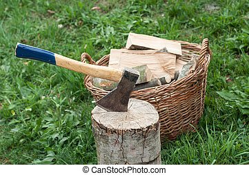 An axe stuck in a log in front of basket with logs fire - An...