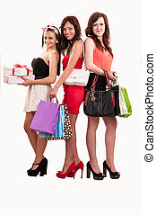 group of three happy young women out of shopping with colored bags and gift boxes