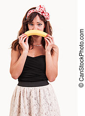 Young woman holds up a banana to her mouth, show an sad face