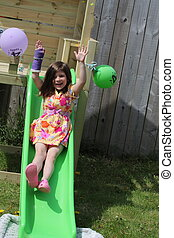 Young Girl on slide - Young girl with broken arm having fun...