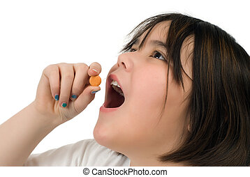 Girl Taking Vitamin C - A young girl taking a chewable...