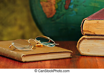 Education - Old books and glasses on desk with globe