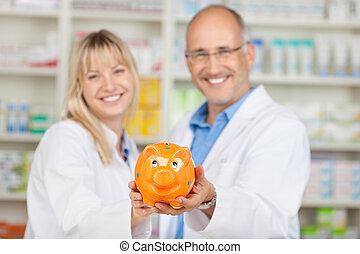 Pharmacists Holding Yellow Piggybank In Pharmacy - Portrait...