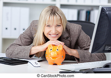 Businesswoman With Piggypank At Desk - Portrait of...