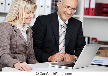 two colleagues looking smiling at laptop - male and female...
