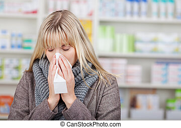 Customer Suffering From Cold In Pharmacy - Young female...