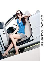 Pretty woman sits in the cabriolet with side door opened -...