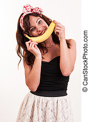 young woman holds up a banana to her mouth, imitating a smile on