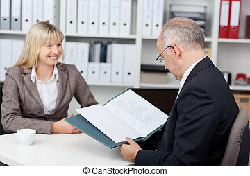 manager reading woman´s cv at office desk
