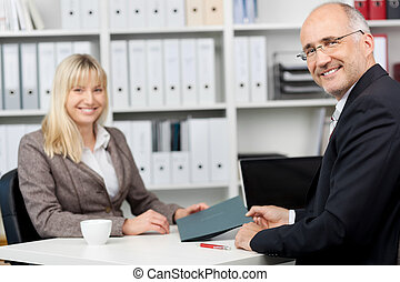 Businessman And Female Candidate Sitting At Desk - Portrait...