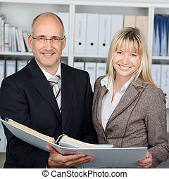 Businesspeople Holding Binder In Office - Portrait of happy...