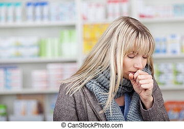 Female Customer Coughing In Pharmacy - Young female customer...