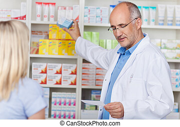 Pharmacist Taking Out Prescribed Medicine For Customer -...