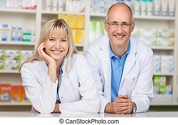 Pharmacists Leaning On Pharmacy Counter - Portrait of male...