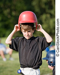 Little Boy Putting on Helmet Getting Ready to Hit