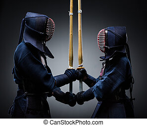 Two kendo fighters with shinai opposite each other Japanese...
