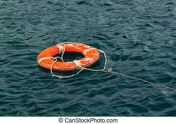 Red life buoy in the water - Safe water support aid circle...