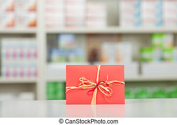 Gift Wrapped In Red Paper And Bow At Pharmacy Counter -...