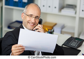 businessman reading document while calling on the phone