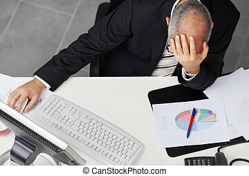 Businessman With Hand On Head At Desk - mature businessman...