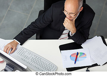 Businessman Using Computer At Office Desk - High angle view...