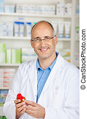 confident smiling pharmacist holding a medicine bottle