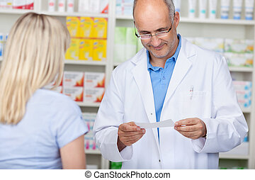 male pharmacist reading prescription