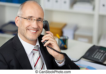 Businessman Using Landline Phone At Desk - Portrait of happy...