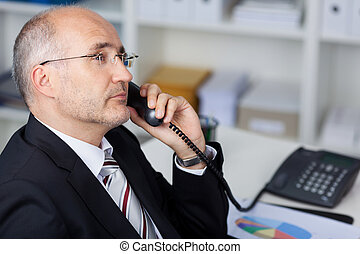 serious manager at the phone - serious manager using the...