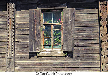 window with flowers in wooden house , russian countryside