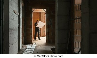 Architect with plans in new house - Engineer at work in...