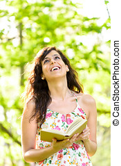 Happy woman reading book on spring - Happy woman reading and...