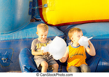 Young boys happily sharing a large cotton-candy ball sitting...